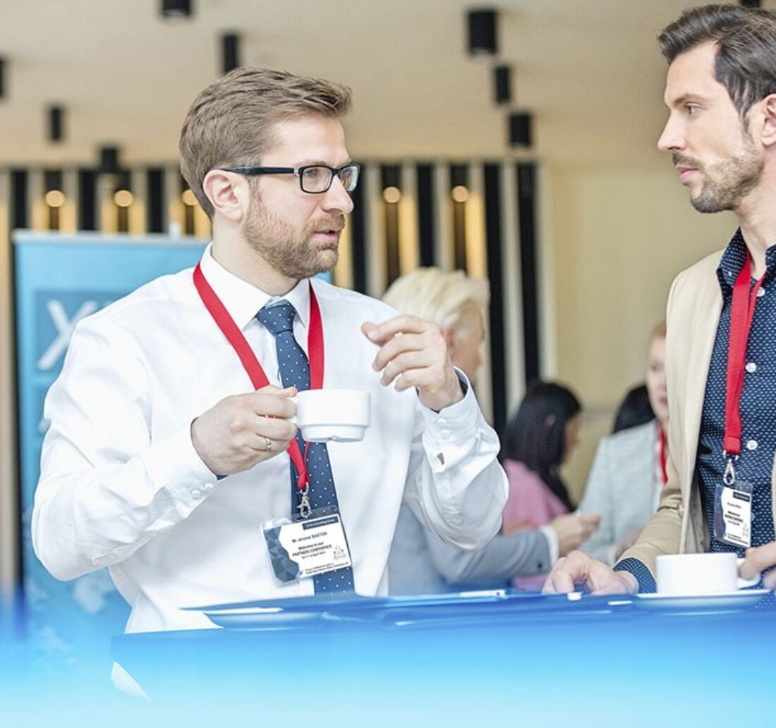 discussion between two men at a trade show wearing their event badge around the neck